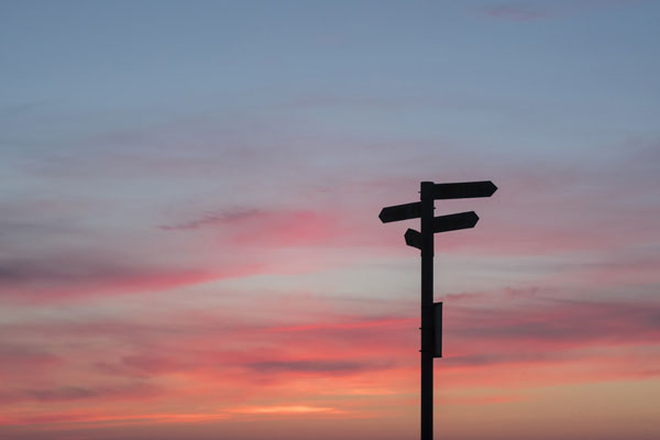 directional sign in the sunset