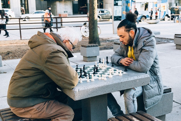 Young and old man playing chess
