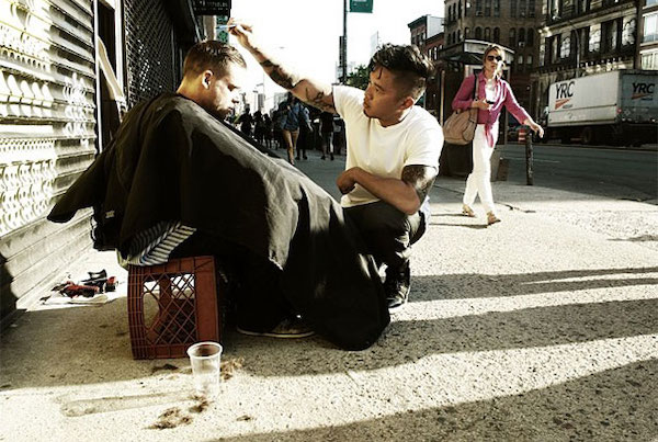Man giving haircut to homeless person