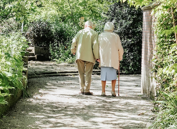 Elderly couple walking holding hands