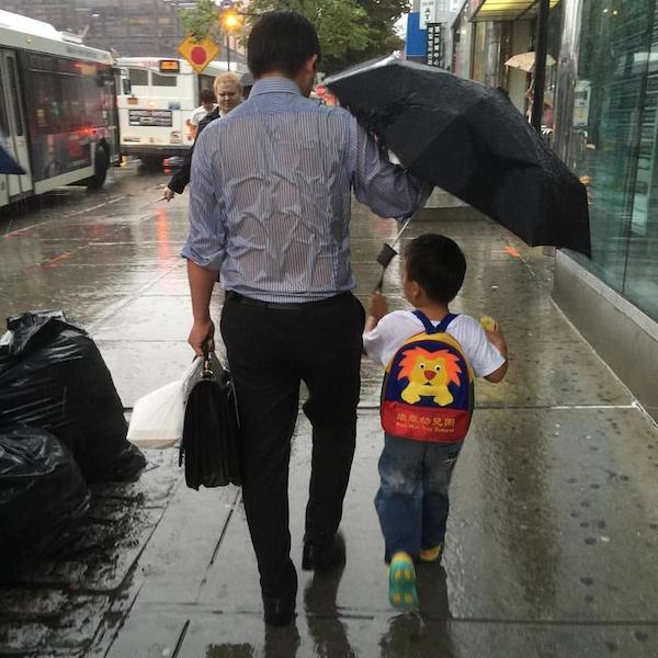 Father covering son from rain