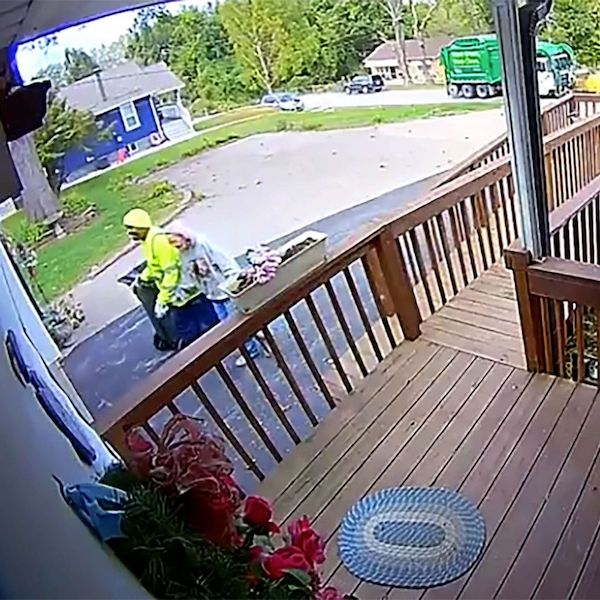 Sanitation worker helping 88-year-old woman
