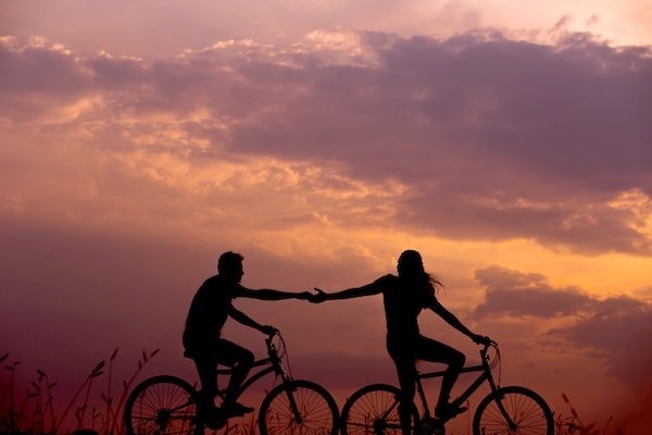 Two People Riding Bikes in the Sunset
