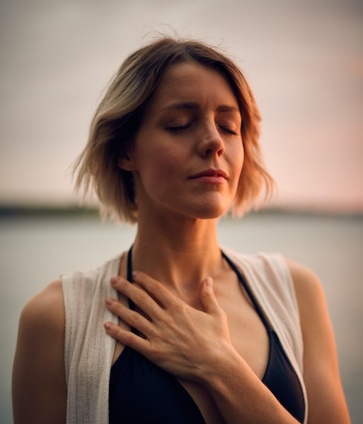 Woman Meditating With And Over Heart