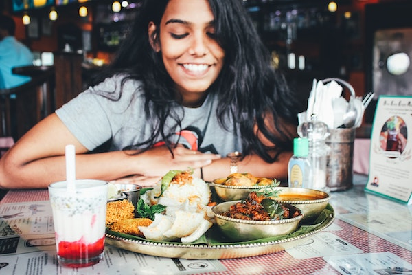 Woman Smiling Over Plate of Food