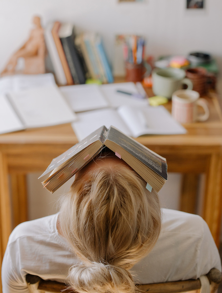 Woman Feeling Anxious With a Book Covering Her Face