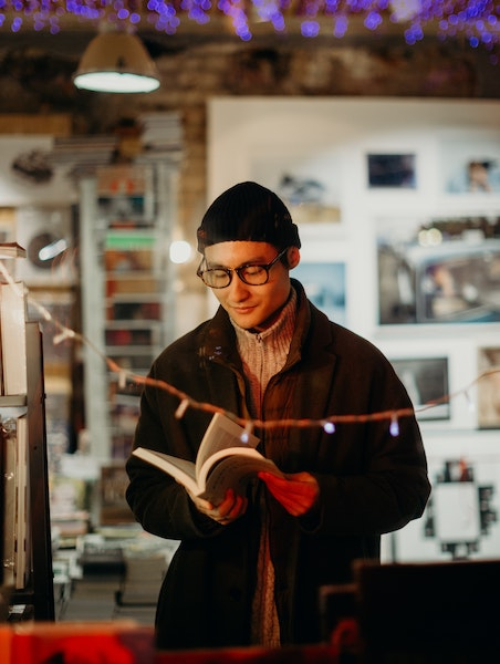 Man Flipping Through Book in Bookstore
