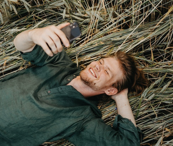 Man Laying on Grass Talking on Phone Video Chat