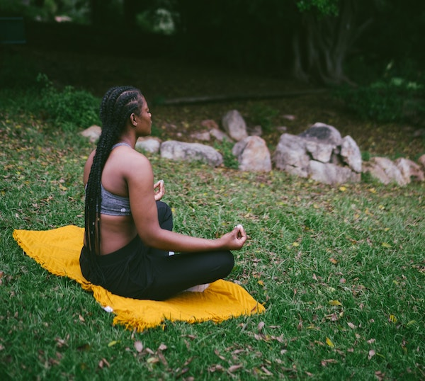Woman Meditating on the Grass