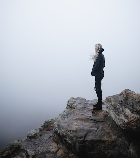 Woman Overlooking Fog While Standing on Rocky Cliff