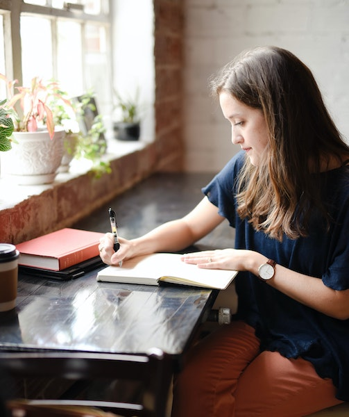 Woman Sitting Inside Writing in Journal