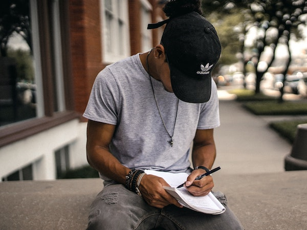 Man Sitting Outside Writing in Journal