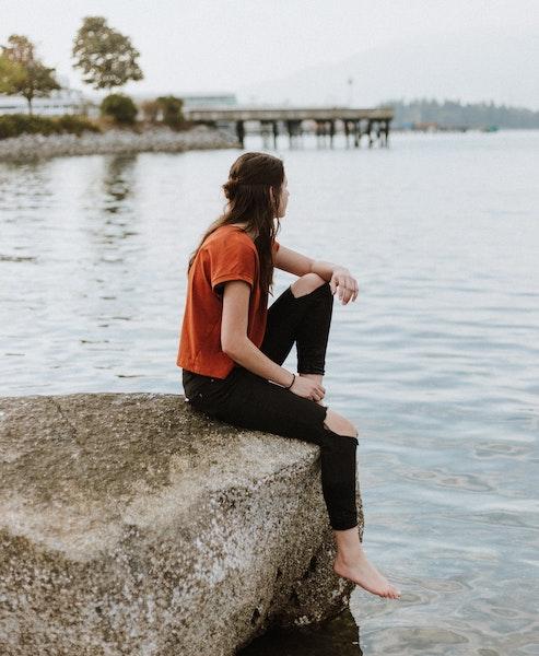 Woman Sitting on Rock Gazing at Peaceful Water