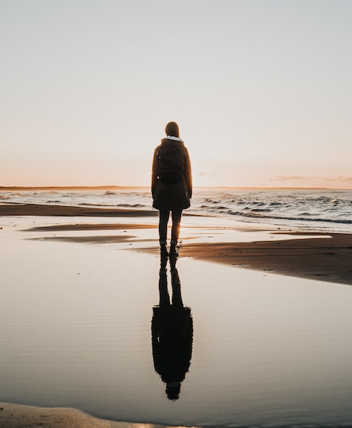 Reflection of Person Standing on Beach