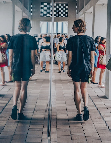 Person Walking by Mirror Looking at Reflection