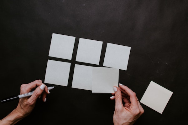 Person Organizing To-Do List on Post-it Notes