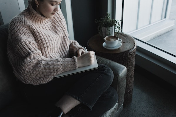 Woman Sitting on Couch While Writing in Journal