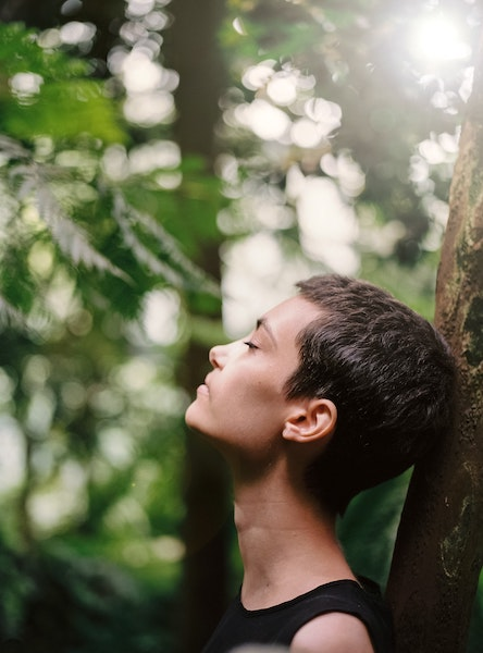 Woman Standing Next to Tree Taking Deep Inhale