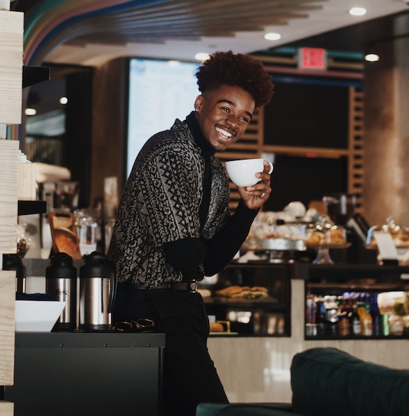 Man Smiling While Drinking Coffee